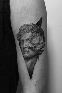 Sculpture head and rose tattoo on the left upper arm.