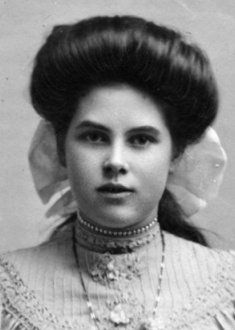 1914- Many Edwardian hairstyles involved padding. The crescent shaped padding for a Low Pompadour went from ear to ear over the top of the wearers head. The hair was taken from the forehead hairline straight over the pad to the back where it was retained by whatever method the wearer chose.  These methods included a bun, cottage loaf , coils or simply tied.   It was the front appearance which mattered most.  Women who wore a full Pompadour hairstyle for formal occasions could put their hair in a Low Pompadour for daily wear.