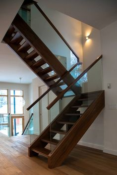 Walnut freestanding stairs with open risers and glass railings by Accurate Stairs and Railings.