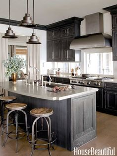 Iron bar stools and iron pendants paired with dark gray cabinetry. Design: Susan Drake