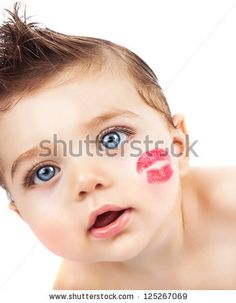 Picture of small pretty kid with red lipstick kiss on the cheek, closeup portrait of cute baby boy isolated on white background, curious toddler with open mouth looking in the camera, Valentines day - stock photo