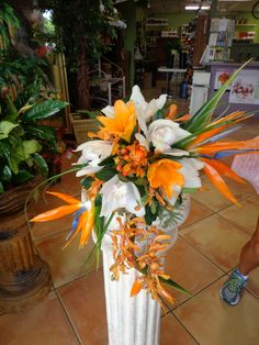 Cascading tropical bridal bouquet of Birds of Paradise, Cymbidium Orchids and Mokara Orchids. Floral designs by China Rose Florist, Marco Island Fl.