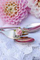 Kuchengabel mit Rosenknospe auf weißer Spitzendecke und rosa Dahlienblüten im Hintergrund