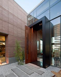 Expansive wood walls and smooth stepping stones lead to the front of this modern home from assemblageSTUDIO. Here, a foyer comprised of beautiful glass panels and an elongated door offers a sleek and serene entrance.