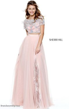 Sherri Hill 50857 is a two piece evening gown with a beaded illusion short sleeve bodice and a layered skirt with lace peeking out of the high slit.