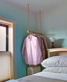 a dowel and ropes make a great clothing rack - note that they maximized space by hanging it above the radiator #storage #closet #smallspaces