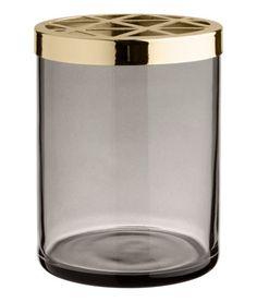 Rosa. En tandborstmugg i glas med avtagbart, hålmönstrat lock i metall. Diameter 7,5 cm, höjd 10 cm.