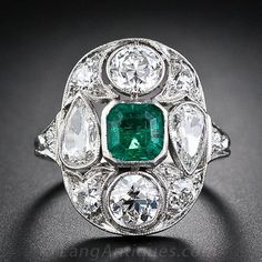 A cushion-shaped arrangement comprised of a central emerald-cut emerald with a pair each of bright-white pear-shape diamonds, pointing in opposite directions, and European-cut diamonds is further embellished with six European-cut diamonds in this glittering platinum original Art Deco ring from the 1920s. Stunning!