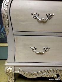 Here's a little bombe dresser redone with Annie Sloan Chalk Paint Paris Grey on the body, Paris Grey & Old White Striae on the drawers, and Graphite underneath silver leafing on the details. The entire piece was triple waxed--first Annie Sloan Clear Soft Wax to seal it, Dark Soft Wax to antique it, and another coat of Clear Soft Wax to finish it up!