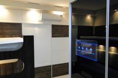 Dormitório tendo roupeiro com TV embutida e portas de alumínio com vidro preto