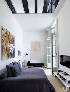 A Hästens bed faces Jasper Morrison marble tables from Galerie Kreo in the master bedroom of a Paris apartment; suspended from the ceiling is a panel by Liam Gillick, and above the headboard is an ink-jet-on-canvas work by Richard Prince.