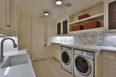Lovely laundry room features an enclosed washer and dryer placed under built in shelves flanked by metal grille cabinets.