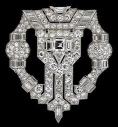 Art Deco platinum and diamond dress clip Stunning modified cartouche form dress clip, displaying a single center asscher cut diamond, approximately .45 carats, framed on either side by a baguette cut diamond, approximately .20 carats, classic pave set diamond Deco surround accented by baguette cut diamonds a single trapezoid cut diamond, kite cut diamond, and finishing in a 'dart' cut diamond. Serial no. 3361 on verso. Total weight approximately 9 carats.
