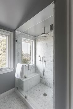 Amazing bathroom features a walk-in shower accented with a gray ceiling adorned with a rain shower ...