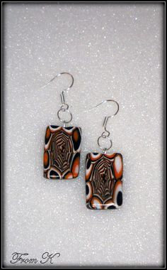 Halloween theme.... This one of a kind pair of earrings is made with polymer clay. Created by using the mokume gane technique with many layers of transitioning copper, white and black palettes. The design is modern, so it can be worn with both casual and formal outfits. The polymer clay is finished by sanding, polishing and varnished to a soft shine. About 2,5 cm long with the ear piece 10.00 Ron