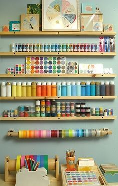 Great way to organize the paints with narrow but long shelves so everything is easy to find and adds color to the room.