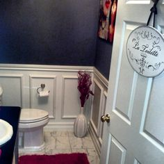 This is our first home renovation and design project in our new home. The bathroom was completely gutted.  - New 8x8 tile - Added wood trim to create a wainscoting effect (painted white) - Added mini chandelier to the center ceiling - Created tabletop vanity with stainless plumbing - Added brushed nickel hardware - New toilet - Off-black wall paint - Breakaway hinges and larger door frame make this bathroom ADA compliant - Black, white and magenta accents