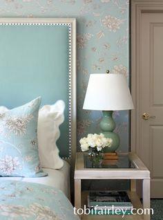 Upholstered headboard, custom floral bedding  Design: Tobi Fairley