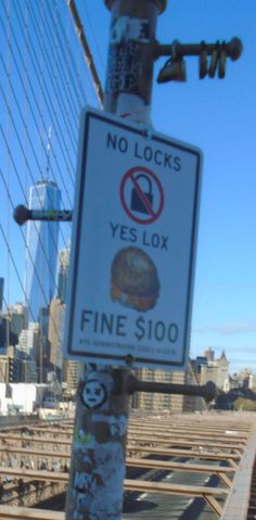 I love the juxtaposition: lock, lox, and nevertheless, there are padlocks just above the sign. If the expectation of locks doesn't make sense to you, look up https://en.wikipedia.org/wiki/Love_lock. They have to be removed because the cumulative effect of so many locks adds a lot of unnecessary weight for the bridge to support.