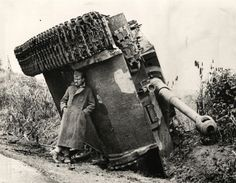 A British soldier hiding from the rain under an overturned Tiger tank. Italy, 1944
