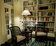 Something's Gotta Give reading nook in corner of living room:dark wicker chairs, bookshelves