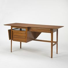 Lot 682: Ico Parisi. desk. c. 1950, mahogany. 60 w x 25 d x 29¾ h in. result: $18,000. estimate: $20,000–30,000. A finely detailed writing desk with three drawers, one shelf, and angled storage below asymmetrical top.