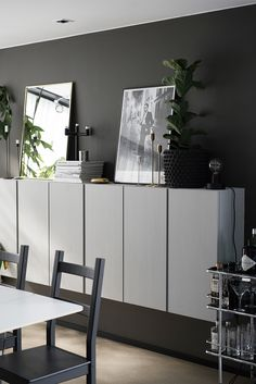 Charcoal grey walls and wallmounted white floating cabinets from IKEA as a credenza
