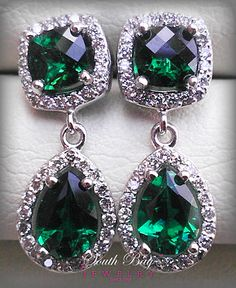 Antique cut emerald earrings accented by a diamond halo.