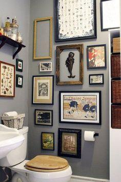 decoração de banheiro lavabo com muitos qradros, gallery wall no banheiro lavabo, parede pintada de cinza, quadros vintage no banehiro