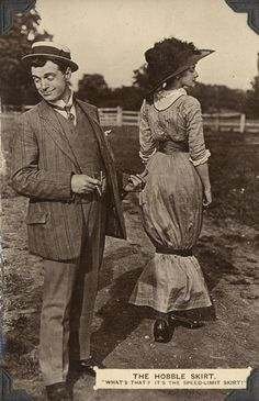 "A postcard (circa 1911) depicting a man and a women dressed in the fashion of the era. Woman wears a hobble skirt, man points to her with his thumb. Caption: The Hobble Skirt ""What's that? It's the speed-limit skirt!"" (Caption makes joke in reference to the fact that such skirts prevented rapid walking.)"