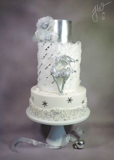 Silver Winter - Silver Winter My last cake of 2014.. There were a couple of late nights with this one. The sparkly and shiny wafer paper poppies with crystal centers as well as the fringed middle tier are techniques I learned from Kara, of Kara's Couture Cakes in her Cake Made class, Wafer Paper Cake Designs. The silver reindeer was fashioned after a Christmas ornament and is made from a mix of fondant, modeling chocolate and a bit of gum paste. Silver leaf snowflakes and dragee snow ...