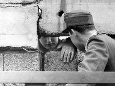 A policeman from West Berlin (r) talks to a citizen from East Berlin (l) through a hole in the Berlin Wall on the 19th of September in 1962.