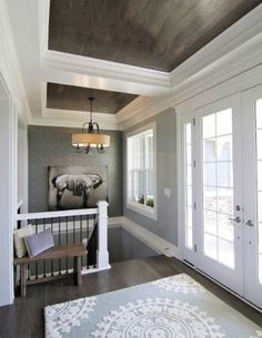 wood paneled ceiling with moldings.