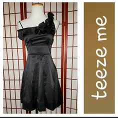 Party Dress! Super cute dress.  Perfect for homecoming, parties,any semiformal occassion.  Black.  Spaghetti strap on right shoulder, wide strap on left shoulder with flower accents.  Ties in back.  Hook and zip closure in back.  Fully lined, crinoline at bottom edge of lining.  Sz 7.  Measurements lying flat armpit to armpit 16in,  waist 14in,  length armpit to hem 26in.  Great condition.  No stains or tears.  From smoke free home. Teeze Me Dresses