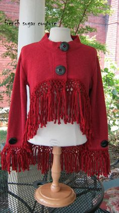 Cozy One-of-a-Kind knit jacket - altered. I love this ruby-red color and I adore the over-sized big black buttons. This garment started out as a plain jacket with two pockets and four buttons down the front. Now its something to talk about. Completely redesigned in shape and look. Its now short in the front and long in the back. I crocheted a loop trim and added gorgeous fringe. I saved the two buttons from the bottom of the jacket and placed them on the sleeves - so perfect.    This saucy…