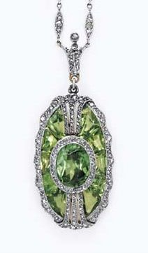 A BELLE ÉPOQUE DEMANTOID GARNET AND DIAMOND PENDANT NECKLACE. The oblong-shaped pendant centring upon an oval-cut demantoid garnet, within a calibré-cut demantoid garnet surround, enhanced by rose-cut diamonds, suspended by a rose-cut diamond foliate bail, to the fine-link chain, spaced by rose-cut diamond navette-shaped links, joined by an old European-cut diamond clasp, mounted in platinum-topped gold, circa 1900, clasp signed Tiffany & Co.