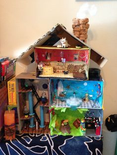 Most recent picture of the entire dollhouse. Note the smoke coming out of the chimney... I also added a vanity table in the bathroom and a dresser with tiny socks in the bedroom. And a floating candle in the library! #Dollhouse