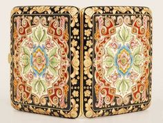 This Russian silver gilt and cloisonné enamel cigarette case is attributed to Feodor Ruckert, Moscow, ca.1896-1908. Both sides are lavishly decorated in multi-color shaded enamel with scrolls, florals, and geometric motifs on a black enamel ground. Source