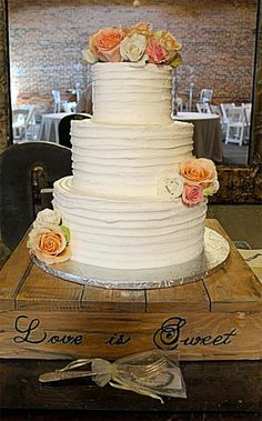 Wooden wedding cake stand with Love is Sweet on the front. You can get whatever you want written on the front in whatever font. The wood can be whatever color you want, too. Also, you can buy legs and make it a table after the wedding! Scroll to number 25 on the page.
