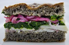 black focaccia with baccalà, marinated onions and buttered spinach