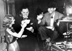 """Ginger Rogers, Jerome Cowan and director Mark Sandrich raise their cups on the set of """"Shall We Dance"""""""