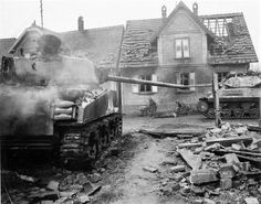 """American tank M4A3(76)W """"Sherman"""", shot down on a city street. In the background is moving fighter tanks 3-in. Gun Motor Carriage M10 (Wolverine). The wall of the job soldiers lift a stretcher with the body of the deceased,1944."""