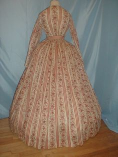 "Back View: c. 1850 thin wool challis dress, bodice boned, fan front; cap sleeves; piping at armhole; offwhite cotton lining in bodice, waistband, unlined skirt trimmed with 3 self fabric tucks, narrow silk bound hem; back hook & eye closure on lining, silk buttons on dress fabric; bust: 32""; waist: 23""; skirt: 36"""