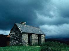 Storm Clouds Pass over a Bluestone Cottage in the Scottish Highlands Photographic Print