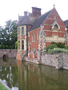 Madresfield Court, nr Malvern, Worcestershire. By P.C. Hardwick, 1863-85, for the sixth Earl Beauchamp. A very large moated house with a much restored 16th century brick wing as the entrance. The rest is bright red brick with half-timbering. An impressive high, narrow, internal courtyard with much carved timber. Arts & Crafts embellishments for the seventh Earl, including the library and chapel.