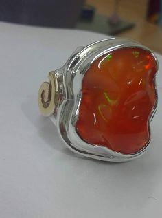 anillo fabricado en plata 950 con unos toques de oro de 14k lleva montado un opalo de fuego mexicano