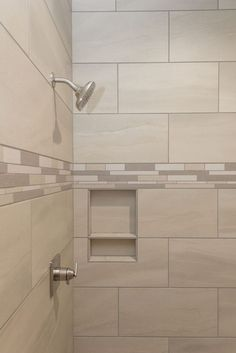 beige tiled shower with accent tile floor and stripe in
