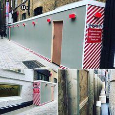 Self supporting wooden hoarding with bespoke graphics self closing fire doors and integrated lights for Sharkey London. Fire Doors, Bespoke, Garage Doors, Creativity, Construction, Graphics, Lights, London, Outdoor Decor