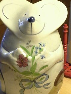 Mouse holding flowers  and cookie with a bite missing cookie jar