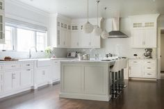 Three crystal globe pendants hang over a light gray kitchen island topped with gray and white quartzite fitted with a prep sink and gooseneck faucet lined with white leather bar stools.